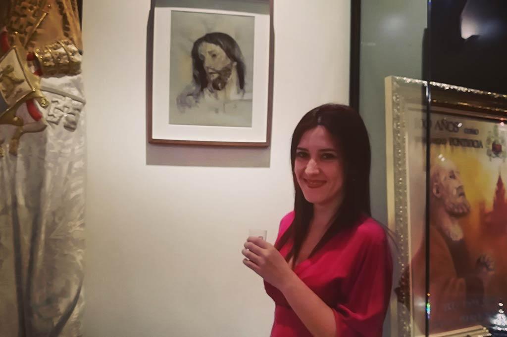 La Artista Plástica jerezana Inma Peña, frente al retrato de Nuestro Padre Jesús del Prendimiento, con el que colabora en la exposición